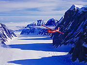 K2 Aviation's Cessna 185 on wheel skis flying over the Ruth Gorge of the Ruth Glacier, Denali National Park, Alaska.