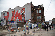 Redevelopment near street art in Hackney Wick in London, England, United Kingdom. Large scale letters covering a promotional mural spell out H W standing for Hackney Wick Street art in the East End of London is an ever changing visual enigma, as the artworks constantly change, as councils clean some walls or new works go up in place of others. While some consider this vandalism or graffiti, these artworks are very popular among local people and visitors alike, as a sense of poignancy remains in the work, many of which have subtle messages.