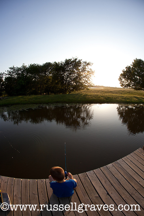 YOUNG BOY ANGLER FISHING FOR BLUEGILL SUNFISH ON A FARM POND