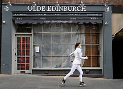 Edinburgh, Scotland, UK. 29 April 2020. Views of Edinburgh Old Town as coronavirus lockdown continues in Scotland. Streets remain deserted and shops and restaurants closed and many boarded up. Scottish Government now recommends public to wear face masks. Woman in face mask runs past closed tourist shop on the Royal Mile. Iain Masterton/Alamy Live News