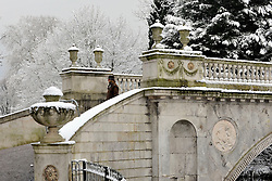 © Licensed to London News Pictures. 10/02/2012, London, UK. A woman walks across The Classic Bridge built for the 5th Duke of Devonshire. People enjoy the snow in the grounds of Chiswick House in West London today 10 February 2012. Chiswick House, undergoing restoration,  is the first and one of the finest examples of neo-Palladian design in England.  Inspired by the architecture of ancient Rome and 16th Century Italy, the third Earl of Burlington built the house as a homage to Renaissance architect Palladio.The cold weather across the UK is set to continue over the weekend.  Photo credit : Stephen Simpson/LNP