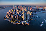 New York from a helicopter over the harbor at sunset.