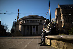© Licensed to London News Pictures. 26/03/2020. Manchester, UK. A saxophonist plays to no one in St Peter's Square in front of Manchester Central Library . Manchester City Centre lies nearly empty during a sunny spring afternoon . The British government has imposed a lockdown on all but essential activities and instructed people to reduce social contact as part of quarantine measures to prevent the spread of Coronavirus ( COVID-19 ) . Photo credit: Joel Goodman/LNP