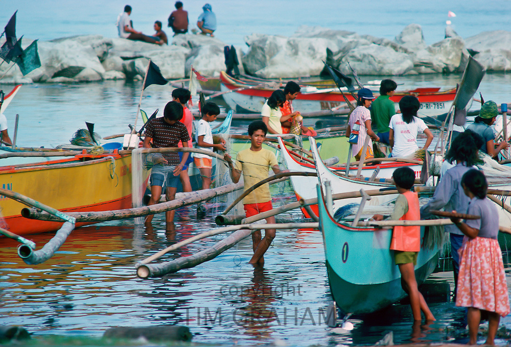 Fishermen bring in their boats and their catch to the fish market in Manila, Philippines