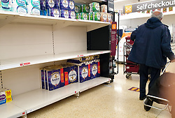 © Licensed to London News Pictures. 28/09/2020. London, UK. A shopper walks past nearly empty shelves of toilet rolls in Sainsbury's supermarket in London as essential items start to run low amidst a possible second lockdown in London due to a rise in COVID-19 cases. The government is considering a 'total social lockdown' for London and parts of the North if coronavirus infection rates do not fall. Number of supermarkets are restricting shoppers from bulk-buying products such as flour, pasta, toilet rolls and anti-bacterial wipes. Photo credit: Dinendra Haria/LNP