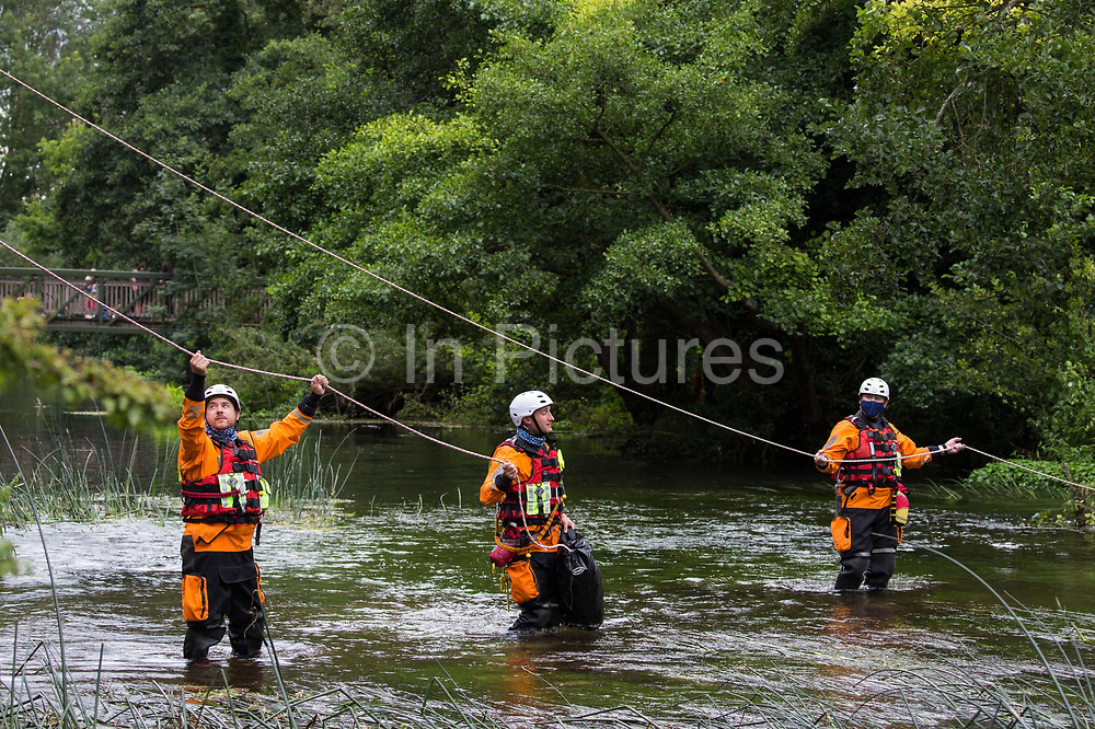 Police officers from Hampshire Police Marine Support Unit stand holding lines in the river Colne during a large policing operation to ensure that environmental activists from HS2 Rebellion did not prevent removal of an ancient alder tree for the HS2 high-speed rail link on 24th July 2020 in Denham, United Kingdom. Officers from the Metropolitan Police, Thames Valley Police, City of London Police and Hampshire Police attended as well as the National Eviction Team.