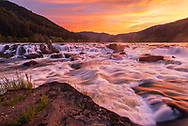 A fiery red sunset casts a warm glow across the waters of the New River at Sandstone Falls in West Virginia.