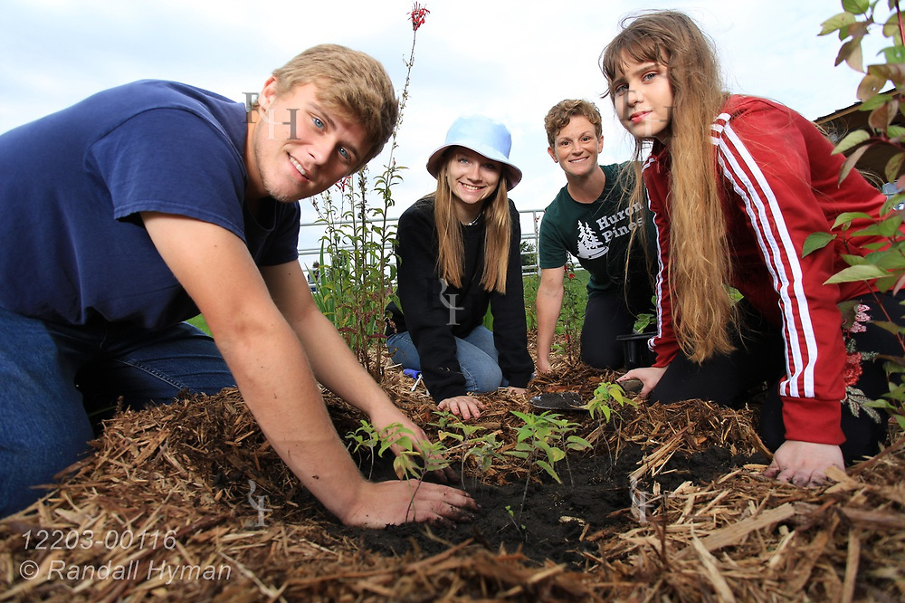 High school environmental sciences students pose with  Huron Pines community program director Abby Ertel while planting wildflowers in bioswale of rain garden at River Side Park in Au Gres, Michigan.