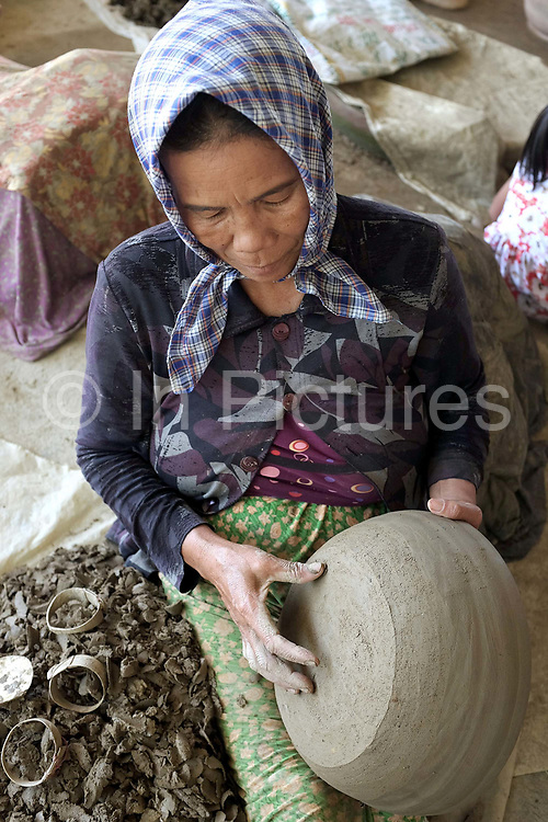 A Hindu Cham woman making ceramic pots using a traditional method in the famous pottery village of Bau Truc in Central Vietnam. Cham potters do not use a wheel to make pots, instead clay is pressed into shape using the hands. Layers of clay are added to the original piece and the potter moves around the object, pressing the clay into the desired shape. They are then put directly in the sun and completely bone dried, making them ready to be fired. Firing is done in an open pit with temperatures going up to 800 degree Celcius. The pots are arranged together and covered with layers of rice straw, which is set on fire.