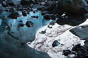 Reflection of the glacier and surrounding mountainside from inside an ice cave within Byron Glacier.