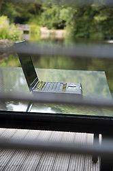 Laptop computer on glass table shot from inside