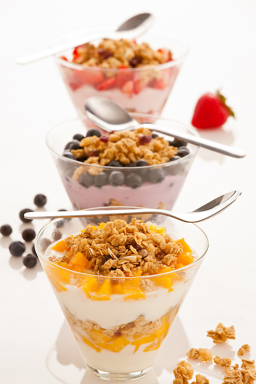 Three fresh Yogurt parfaits in clear glasses with granola and mixed fruits