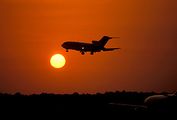 Silhouette of Airplane in Flight at Sunset
