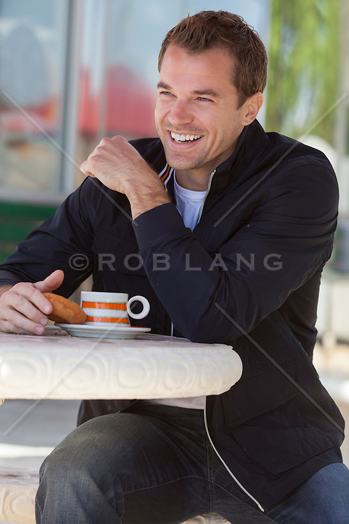 man enjoying a cup and coffee and a donut at a cafe