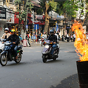 A 44 gallon drum burns with high flames on the side of the road as scooters rush by in Hanoi's Old Quarter.
