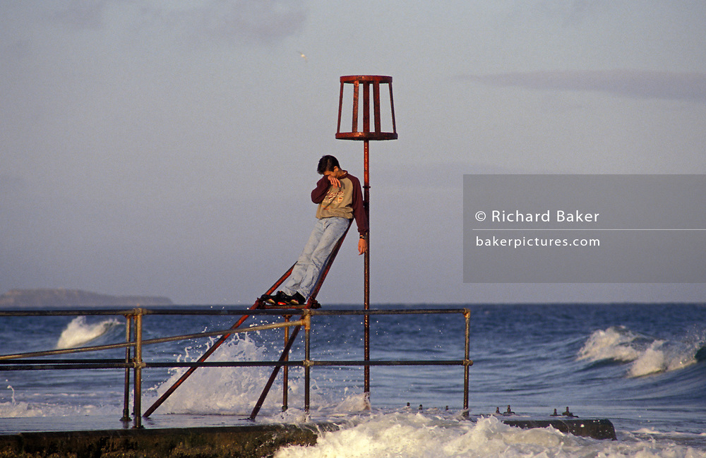As the surf splashes around him, a young man stands on iron railings and wipes his face, on 20th October 1990, in Bournemouth, England.