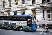 Tour bus with a huge printed photograph of Stonehenge on its side extols its close proximity for tourists in London, United Kingdom.