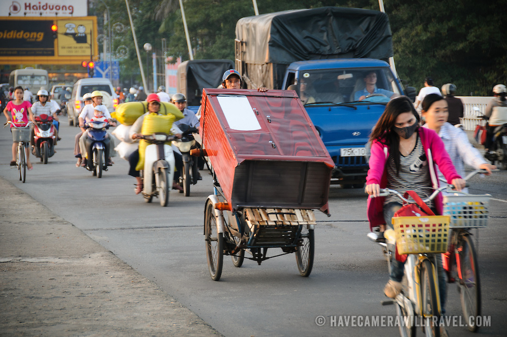 A man on a modified bicycle transports a chest of drawers across Cau Phu Xuan in evening traffic in Hue, Vietnam.