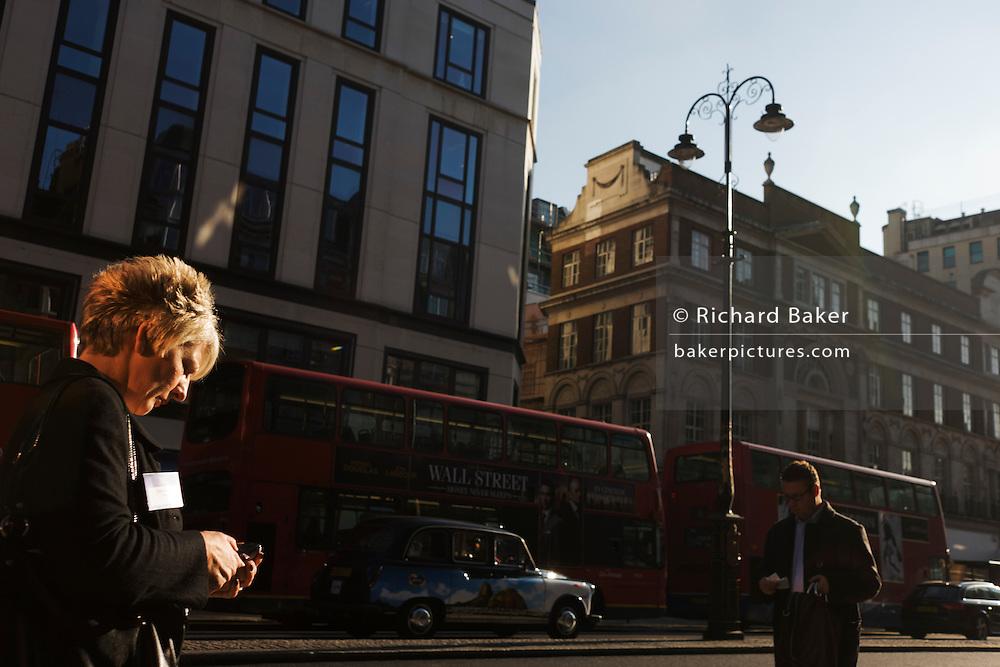 Woman walks along city street in central London.