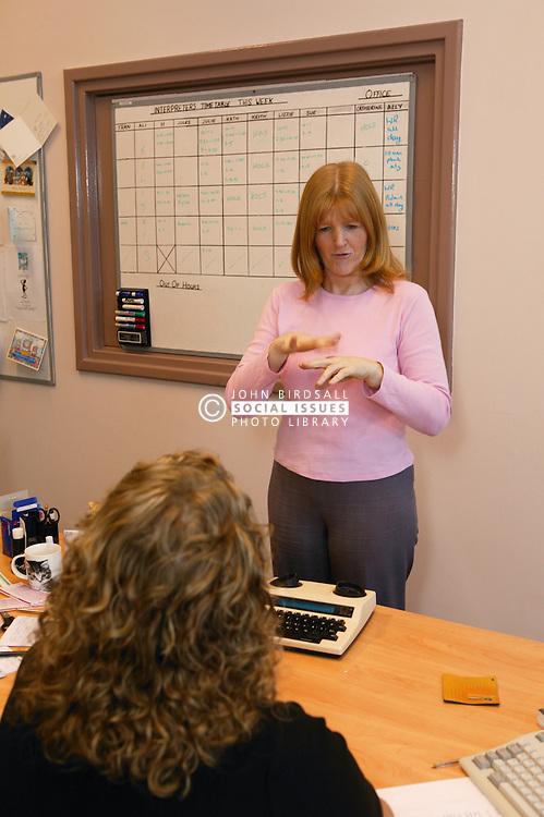Single parent at work signing to her colleague in a meeting,