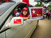 25 OCTOBER 2015 - SHWEPYITHAR, MYANMAR:  A National League for Democracy (NLD) supporter holds up a NLD placard during a party motorcade in Shwepyithar, Myanmar. Political parties are in fill campaign mode in Myanmar (Burma). National elections are scheduled for Sunday Nov. 8. The two principal parties are the National League for Democracy (NLD), the party of democracy icon and Nobel Peace Prize winner Aung San Suu Kyi, and the ruling Union Solidarity and Development Party (USDP), led by incumbent President Thein Sein. There are more than 30 parties campaigning for national and local offices.    PHOTO BY JACK KURTZ
