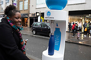 Woman filling up her reusable bottle from a free drinking water fountain on Camden High Street on 14th January 2020 in London, England, United Kingdom. The Mayor of London partnered with Thames Water to install a network of more than 100 drinking water fountains in busy and accessible areas. The fountains are part of measures taken to reduce the single-use plastic water bottles and to provide free access to healthy tap water.