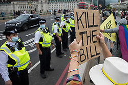 Metropolitan Police officers form a line in front of Kill the Bill activists on Westminster Bridge protesting against the Police, Crime, Sentencing and Courts (PCSC) Bill 2021 as MPs consider amendments to the Bill in the House of Commons on 5th July 2021 in London, United Kingdom. The PCSC Bill would grant the police a range of new discretionary powers to shut down protests, including the ability to impose conditions on any protest deemed to be disruptive to the local community, wider stop and search powers and sentences of up to 10 years in prison for damaging memorials.