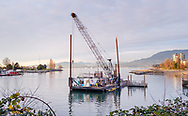 A barge and crane at sunset, framed by the shoreline and distant mountains in Vancouver, British Columbia