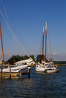 St. Michaels, Maryland--Fishing boats known as skipjacks are mored in the waters of the Miles River. Once a fleet of over two thousand skipjacks existed to harvest the oysters of the Chesapeake Bay. Today there about thirty skipjacks. The skipjack was designated the state boat of Maryland in 1985.