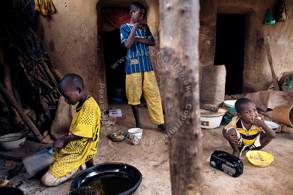 Lukman Maigoro, 6, (right) a young boy suffering from blindness, is having breakfast with two of his siblings in Bagega, pop. 9000, a large village affected by lead poisoning due to the unsafe techniques employed for extracting gold, in Zamfara State, Nigeria. At the age of 4, Lukman became blind due to lead poisoning. He was cured at the Medecins Sans Frontieres (MSF - Doctors Without Borders) clinic in Anka, handling serious cases of lead poisoning referred to them by local clinics in the surrounding villages. It is mainly caused by ingestion and breathing of lead particles released in the steps to isolate the gold from other metals. This type of lead is soluble in stomach acid and children under-5 are most affected, as they tend to ingest more through their hands by touching the ground, and are developing symptoms often leading to death or serious disabilities. The treatment with MSF starts when blood lead level (BLL) samples reach 45 micrograms per decilitre. The Centers for Disease Control and Prevention (CDC) states that a BLL of 5 micro-g/dL or above is a cause for concern. The cycle of medicines lasts for 20 days. After that, the child's blood is tested and a new round of treatment is provided. Treatment can last years, as lead is reduced in the blood, but it persists noticeably within the bones, especially if the patients return to the same polluted environment. Remediation of the affected villages, a campaign of awareness, and the introduction of safer mining techniques are pivotal to the long-term solution of a hazardous trend that has already killed over 460 children, and it is bound to grow in size, fostered by the ever-rising price of gold.