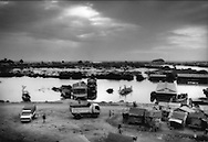 Looking out over squalid settlement to a vast seasonally flooded wetland fringing the vast open waters of Tonle Sap several kilometers distant, Chong Kneas, Cambodia.