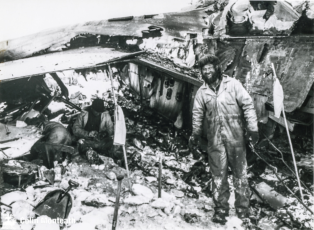DSIR Antarctic Division mountaineer Roy Arbon beside main fuselage, two policemen digging under wing? Final day recovery operation, Air New Zealand crash December 1979.