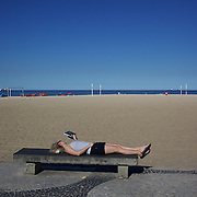A women relaxes and reads a book on a beachside park bench at Copacabana beach, Rio de Janeiro, Brazil. 6th July 2010. Photo Tim Clayton..