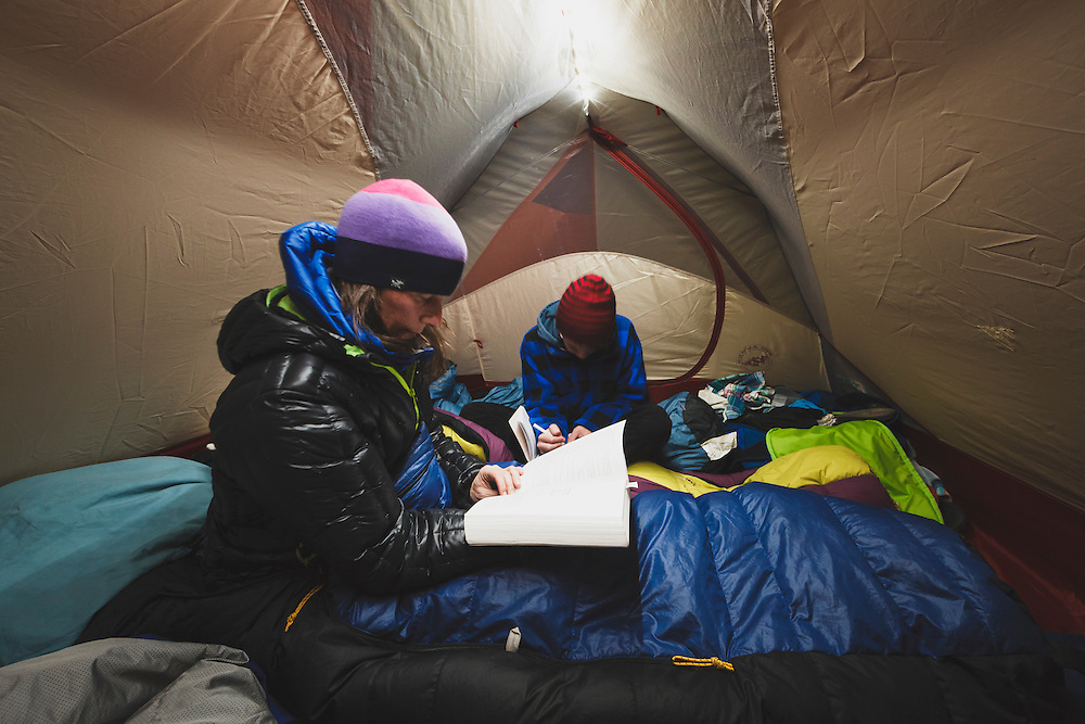 Mother and son read inside a tent while camping.