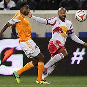 Thierry Henry, (right), New York Red Bulls, crosses the ball while challenged by Warren Creavalle, Houson Dynamo,   during the New York Red Bulls V Houston Dynamo, Major League Soccer regular season match at Red Bull Arena, Harrison, New Jersey. USA. 23rd April 2014. Photo Tim Clayton