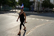 French national equipped with tech colours of the french flag, walks on a street ahead of the match between France and Croatia in the World Cup Final. Paris, France.