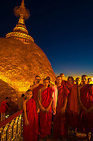 Group of monks stand by the Golden Rock at twilight, Kyaikhtiyo Pagoda, Mon State, Myanmar (Burma)