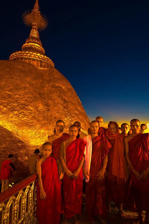 Group of monks stand by the Golden Rock at twilight, Kyaikhtiyo Pagoda, Mon State, Myanmar (Burma)