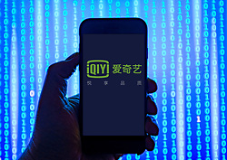 Person holding smart phone with  iQIYi logo displayed on the screen. EDITORIAL USE ONLY