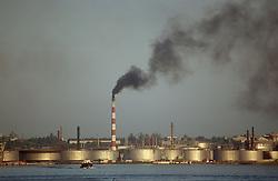 Industrial scene with chimney emitting smoke by the riverside in Havana; Cuba,