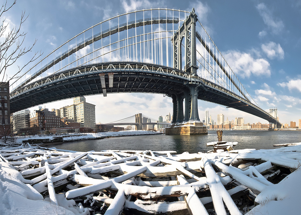 The Manhattan Bridge and the Brooklyn Bridge Park covered with snow, as seen from the old pier in DUMBO, Brooklyn, New York