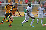 Adebayo Akinfenwa of Wimbledon (r) gets away from Scott Tancock of Newport. Skybet football league two match, Newport county v AFC Wimbledon at Rodney Parade in Newport, South Wales on Saturday 27th Sept 2014<br /> pic by Mark Hawkins, Andrew Orchard sports photography.