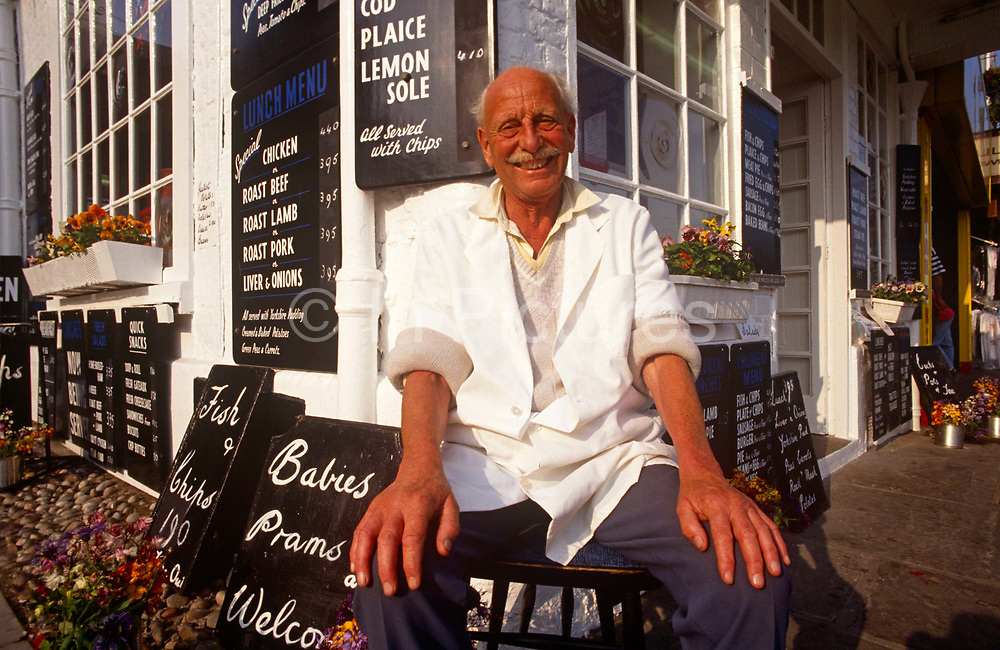 A grinning portrait of a fishmonger from the Princess Cafe on Foreshore Road in the North Yorkshire seaside town of Scarborough. Smiling with bad teeth but with a generous and kind face, the elderly man stands on the corner, outside his traditional seaside business in the centre of town where passing trade from locals and tourists guarantee him an income  - a secure future towards his retirement in the coming years. In the background are signs advertising his produce: Haddock, Cod, and Lemon Sole - all locally caught and served with chips.
