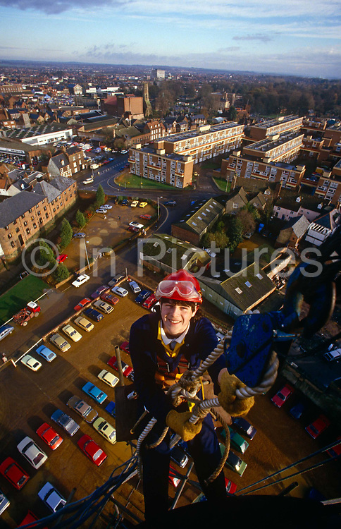 A young apprentice stop near the top of a city centre chimney during a steeplejack course in Kings Lynn, Norfolk. Using an elaborate system of harnesses and pulleys, the young lad is learning the skills to work safely and efficiently at dangerous heights and the town stretches below. Sponsored training is offered through the Steeplejack Industry Training Group Association and CITB-ConstructionSkills for young people aged 16. Applicants for this scheme will have to pass aptitude tests, literary and Maths assessments, and problem solving. Each year, the Steeplejack Industry Training Group and CITB-ConstructionSkills offer 12 places on training courses for trainee steeplejacks and 12 places for trainee Lightning Conductor Engineers.