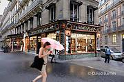 France, Paris, Stationary shop, man washing windows, woman walking