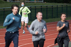 © Licensed to London News Pictures. 04/04/2020. London, UK. A man exercising in a medical face mask and gloves at Paddington Recreation Ground in London, during a pandemic outbreak of the Coronavirus COVID-19 disease. The public have been told they can only leave their homes when absolutely essential, in an attempt to fight the spread of coronavirus COVID-19 disease. Photo credit: Ben Cawthra/LNP
