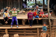Burma/Myanmar. Akha man and children sitting on a terrace of a house.