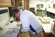 Inside a small trailer-based field station, biologist Travis Livieri records data on a Black-footed ferret (sedated on table at right), near Wall, South Dakota