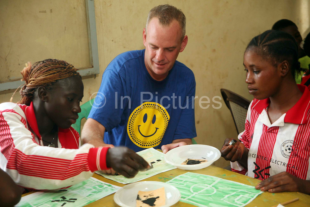 Norman Cook aka Fatboy Slim takes part in a Coaching for Hope art class with the girls and boys from the SOS orphanage outside Bamako, Mali.  Their project for the session is drawing a pitch with the teams playing. Norman is the patron for the charity Coaching for Hope. Coaching for Hope is a project set up to promote awareness of HIV and AIDS through football.