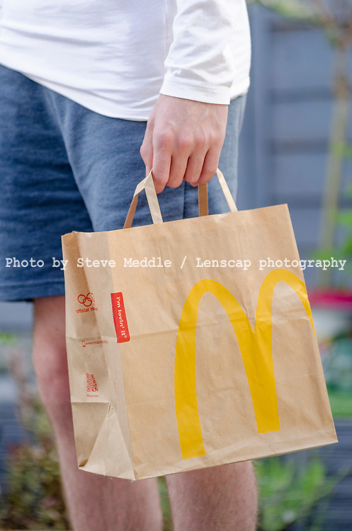 London, England - May 30, 2017: Close up of a McDonald's Take Away Food Brown Paper Bag,  McDonald's is a fast food restaurant chain founded in 1940.